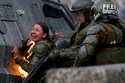 A riot police officer on fire, reacts during a protest against Chile's