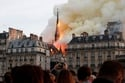 Smoke billows as fire engulfs the spire of Notre Dame in Paris...